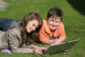 Smiling children with a laptop